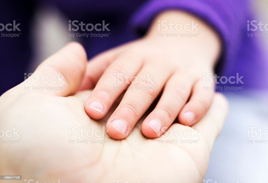 Child placed hand in palm of father's hand stock photo