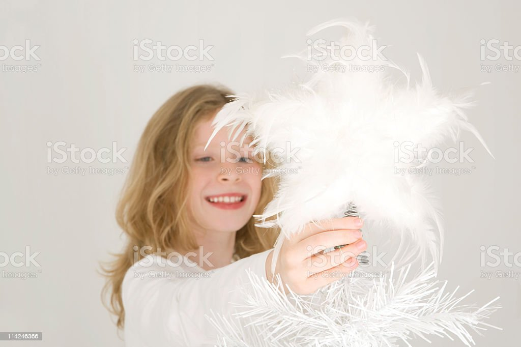 Child places white star on Christmas tree royalty-free stock photo