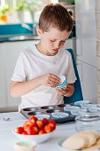 Child placing cupcake forms in baking tray