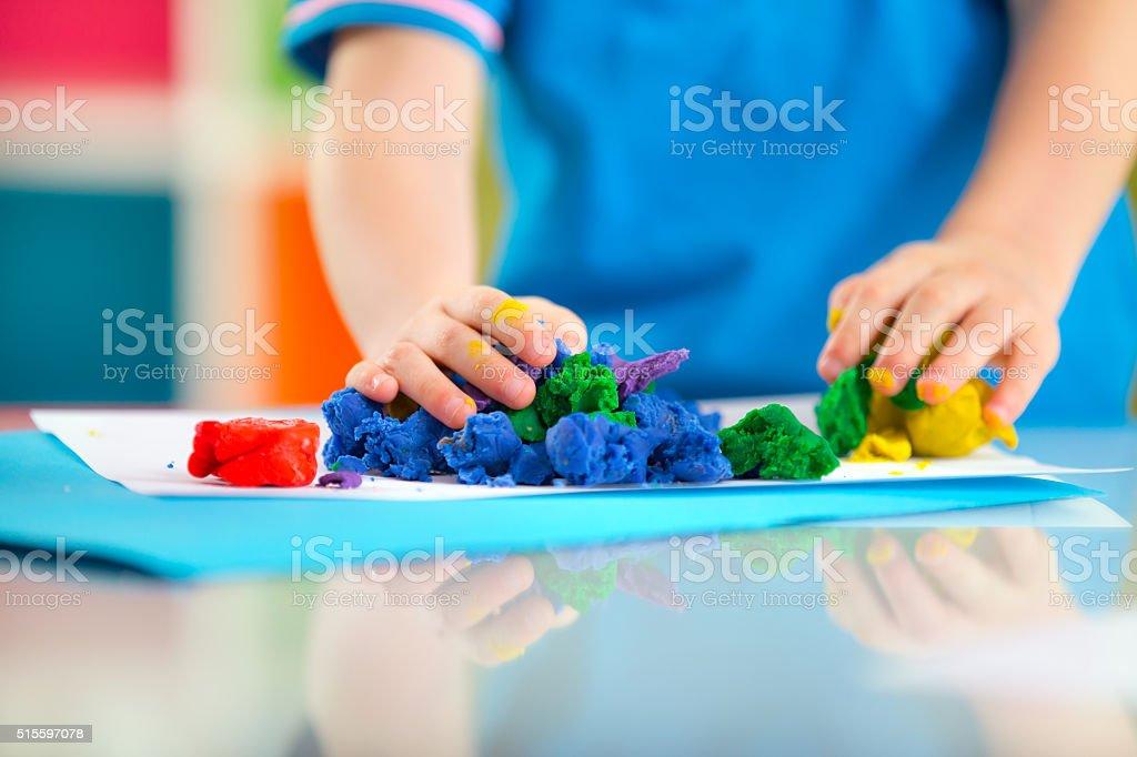 Child play with plasticine stock photo