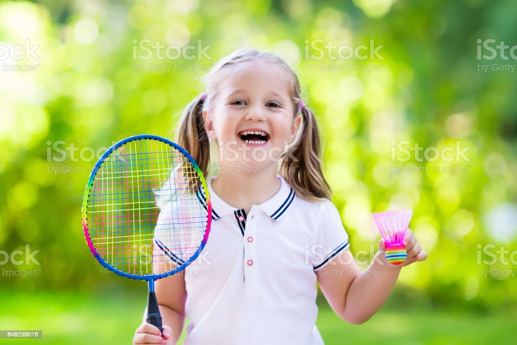 Child playing badminton or tennis outdoor in summer stock photo