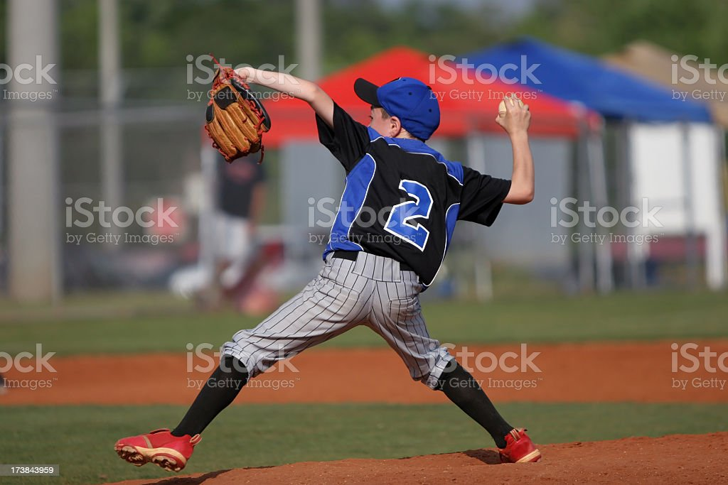 Child playing baseball and throwing ball stock photo