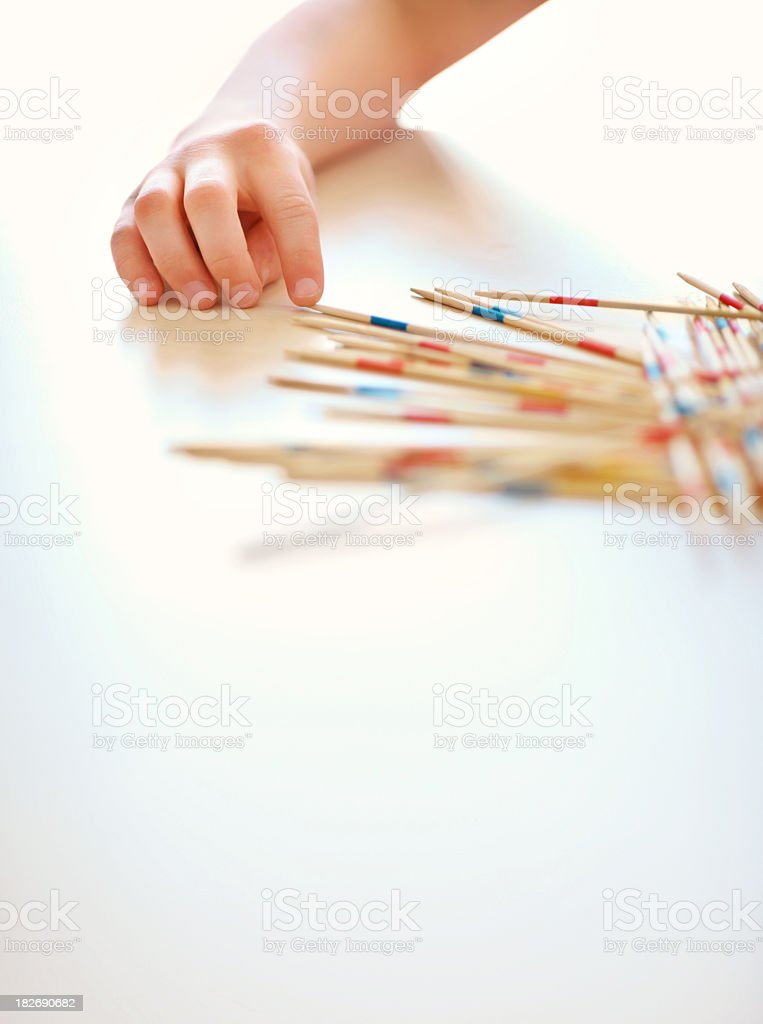 Child playing game of pick a stick stock photo
