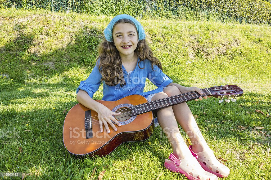 Child playing guitar outdoors royalty-free stock photo