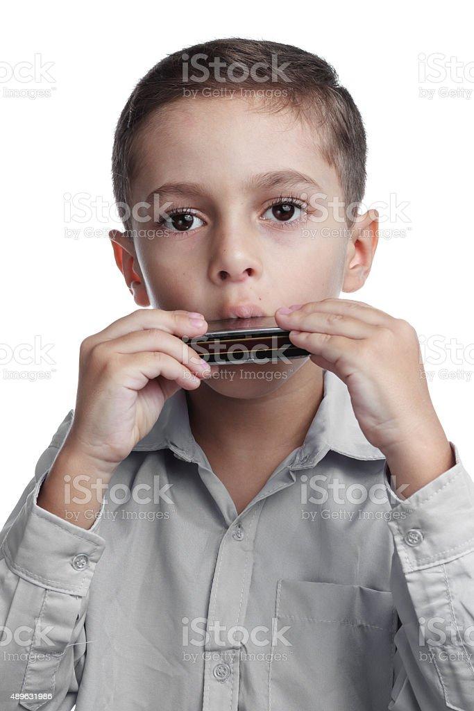 Child playing harmonica stock photo