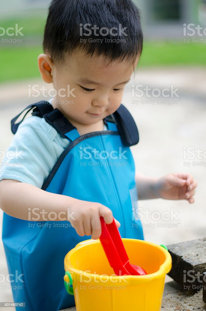 Child playing in sand Box stock photo