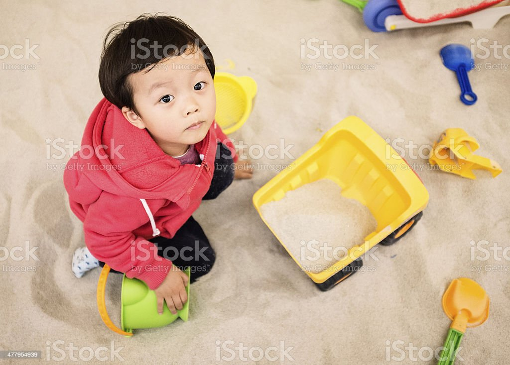 Child playing in sand pit stock photo