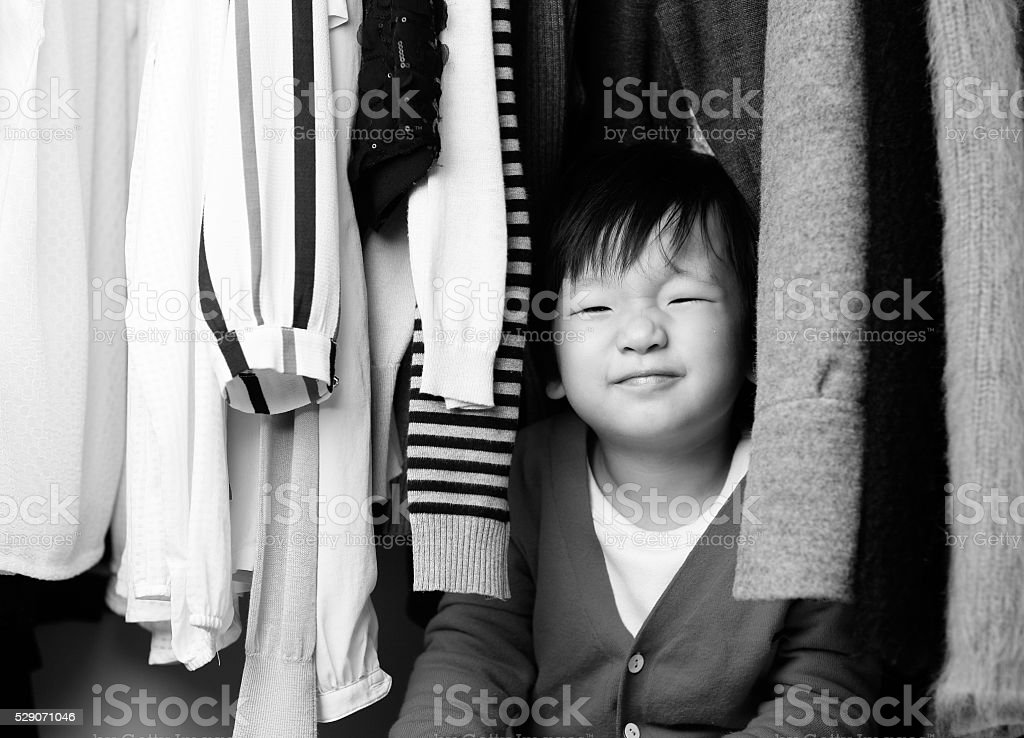 Child playing in the closet stock photo