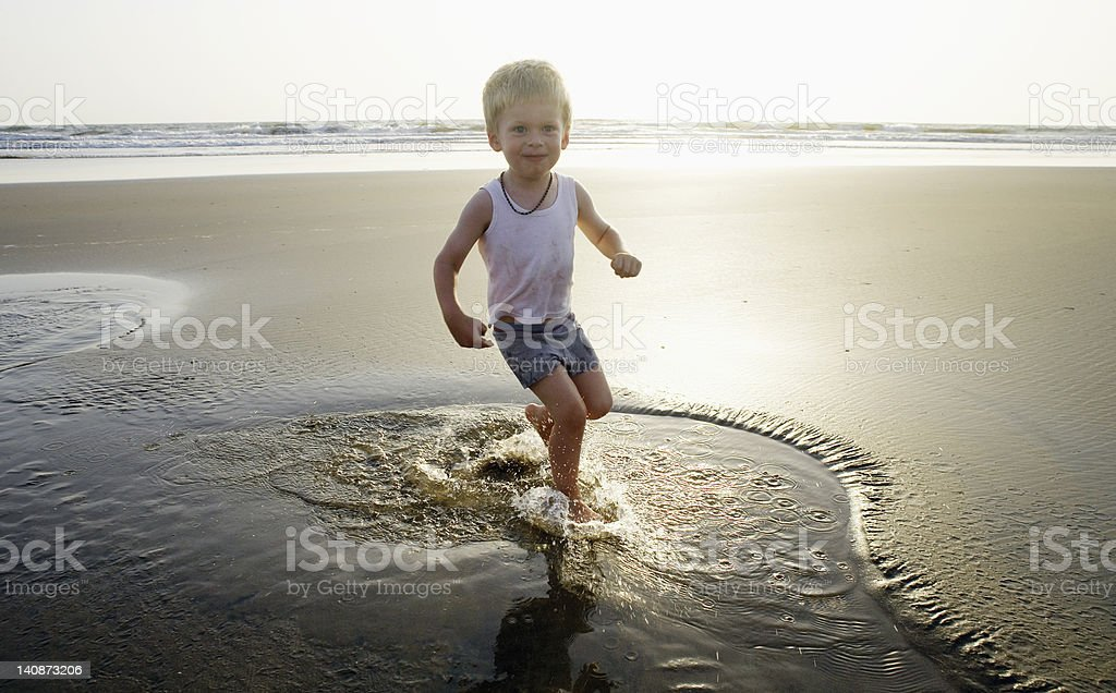 Child playing in water at beach stock photo
