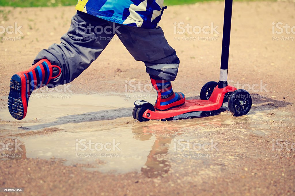 child playing in water puddle, kids outdoors stock photo