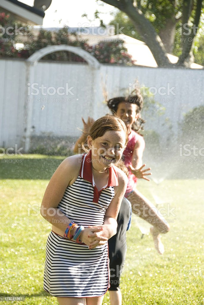 Child Playing in Yard with Water from Sprinklers royalty-free stock photo