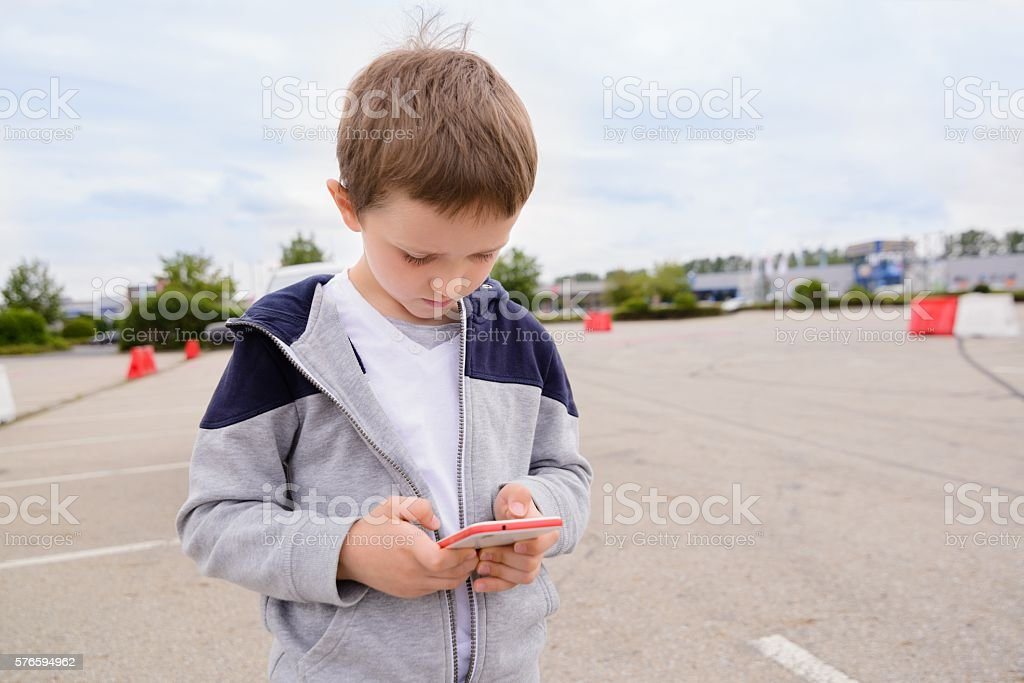 Child playing mobile games on smartphone on the street stock photo