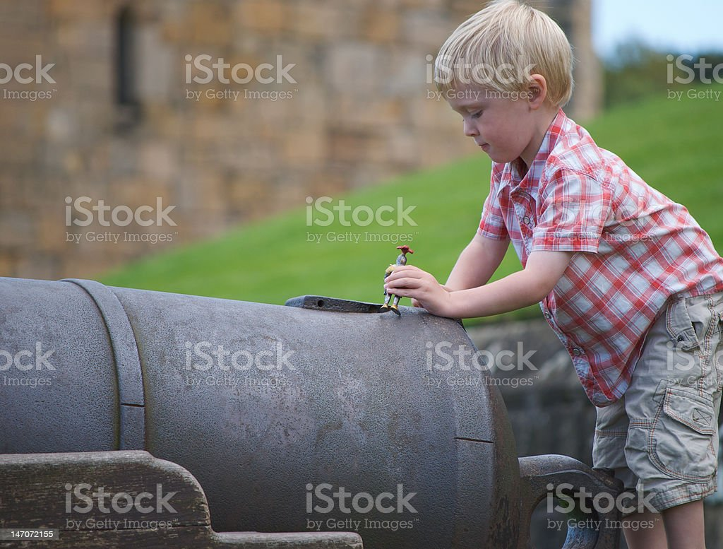 Child playing on cannon at Alnwick Castle, Northumberland stock photo
