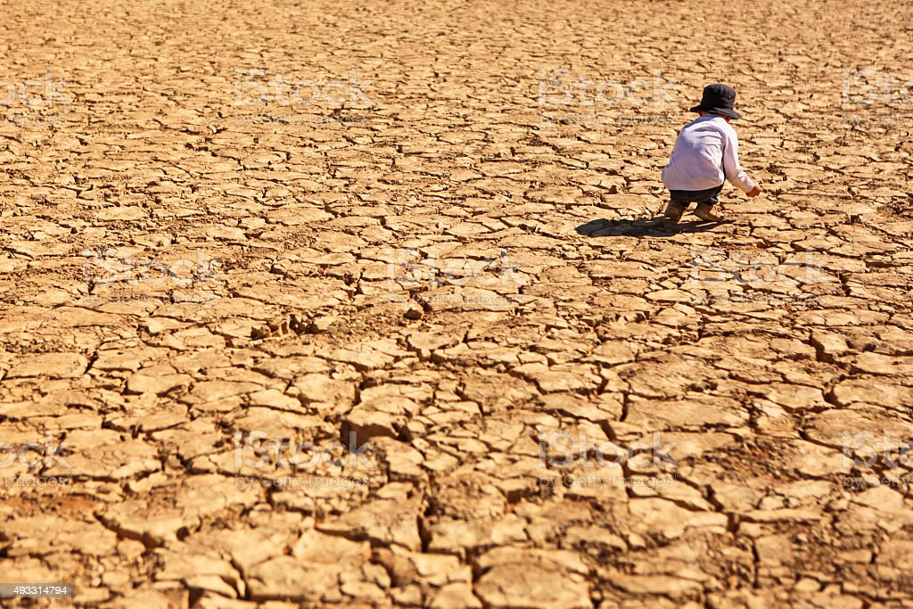 Child Playing on Dry Parched Desert Land stock photo