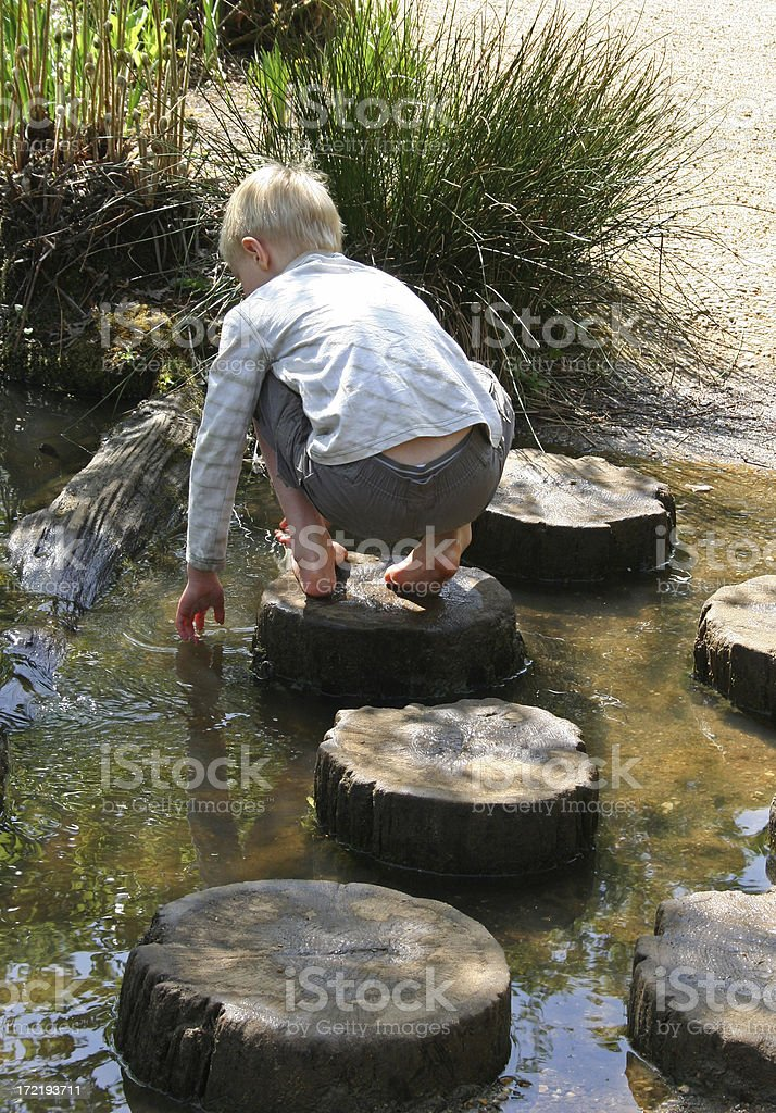 Child playing stepping stones royalty-free stock photo