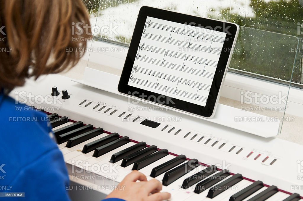 child playing the piano with iPad as sheet of music royalty-free stock photo