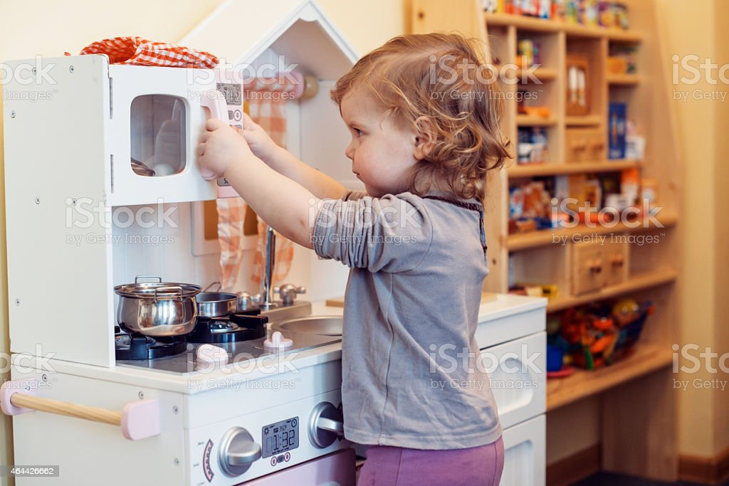 A child playing with a fake kitchen stock photo