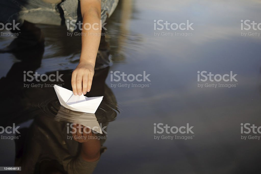Child playing with a paper boat in a puddle stock photo