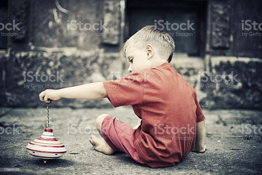 Child playing with a spinning top royalty-free stock photo