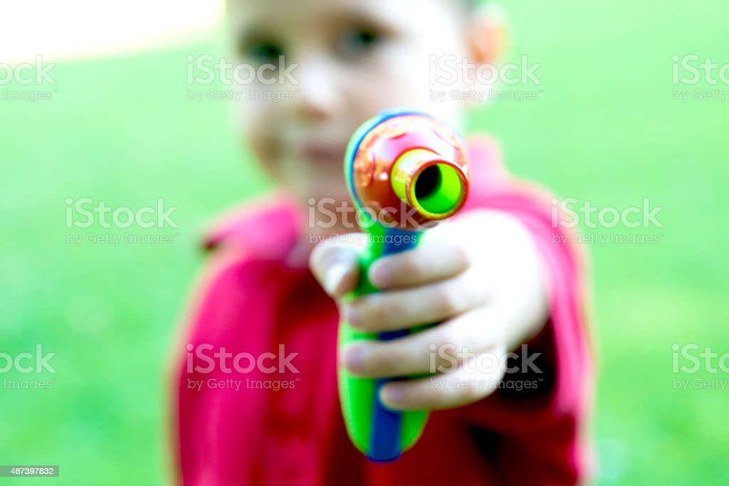 Child Playing with a Toy Gun stock photo