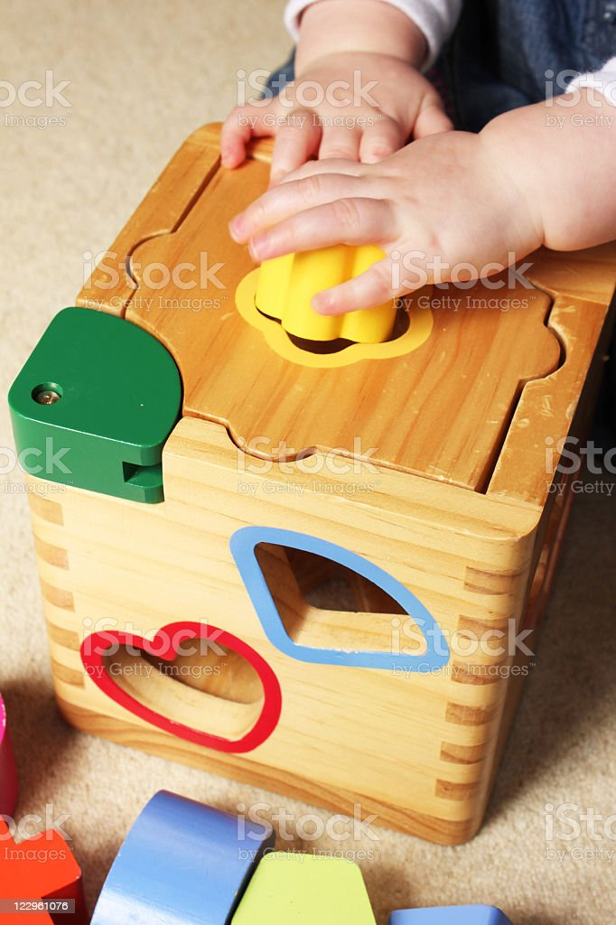 A child playing with a wooden shape sorter stock photo