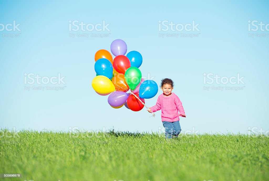 Child playing with balloons. stock photo