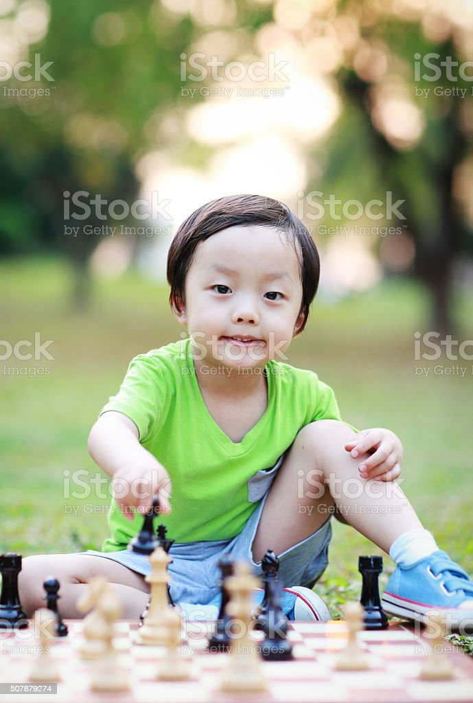 Child playing with chess stock photo