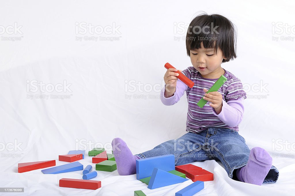 Child Playing with Colorful Blocks on White Background royalty-free stock photo