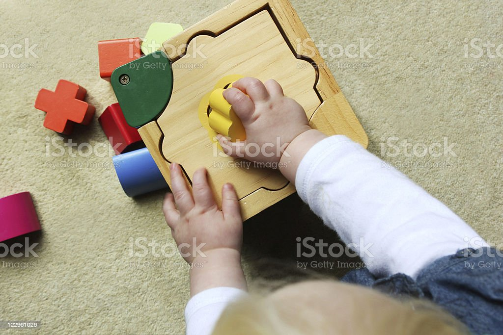 Child playing with colorful volumes of different shapes stock photo