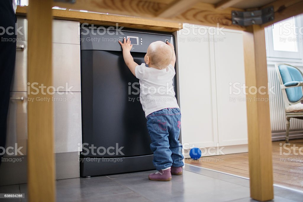 Child playing with dishwasher while parents cooking stock photo