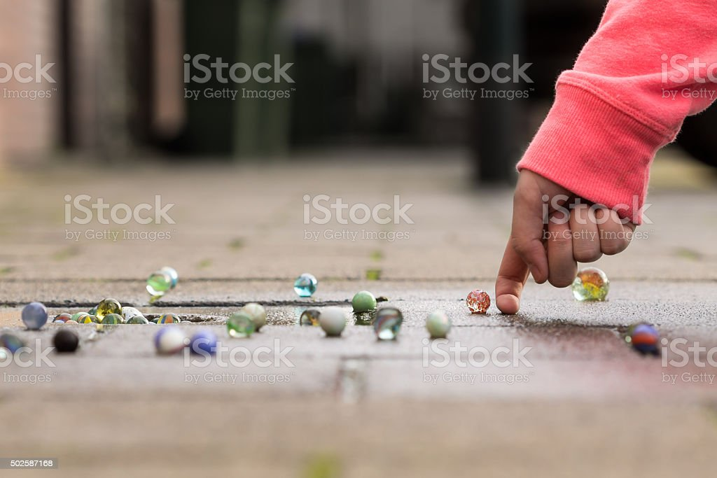 Child playing with marbles on the sidewalk. stock photo