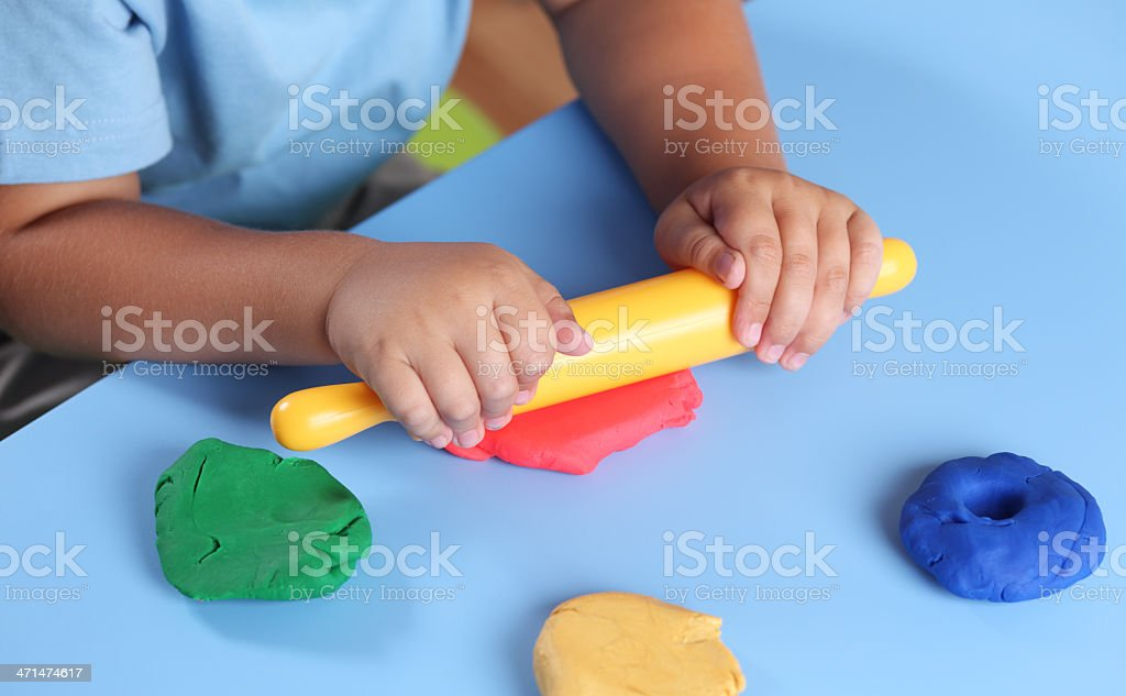 Child playing with modeling clay stock photo