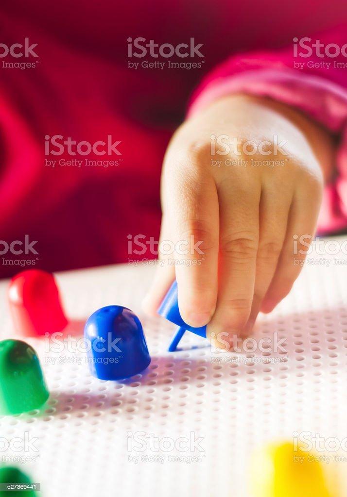 Child playing with mosaic peg board closeup stock photo