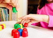 Child playing with mosaic peg board with teacher