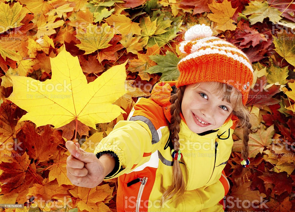 Child playing with orange leaves in the Autumn royalty-free stock photo