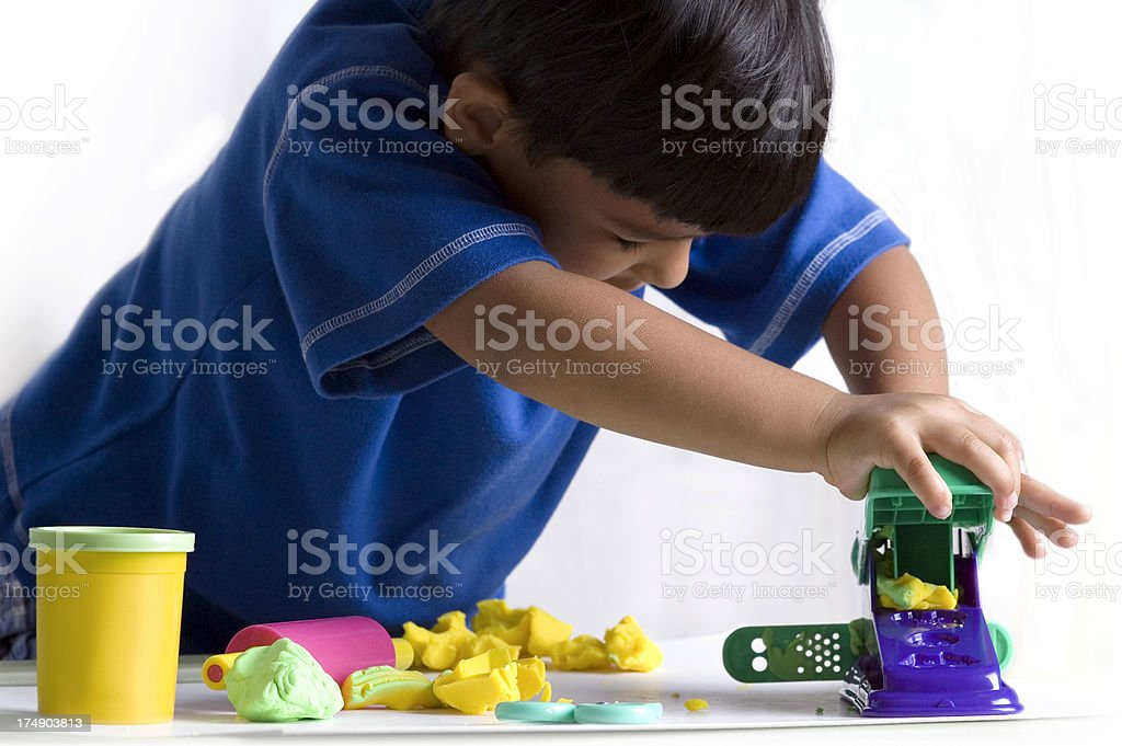 child playing with playdough stock photo