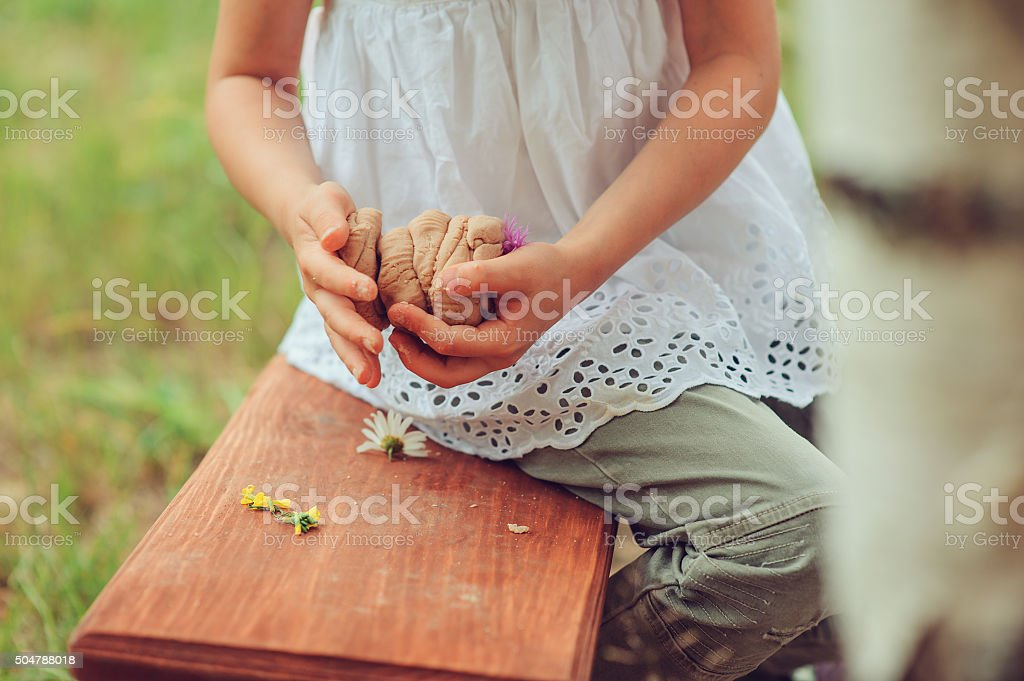 child playing with salt dough and making cakes stock photo