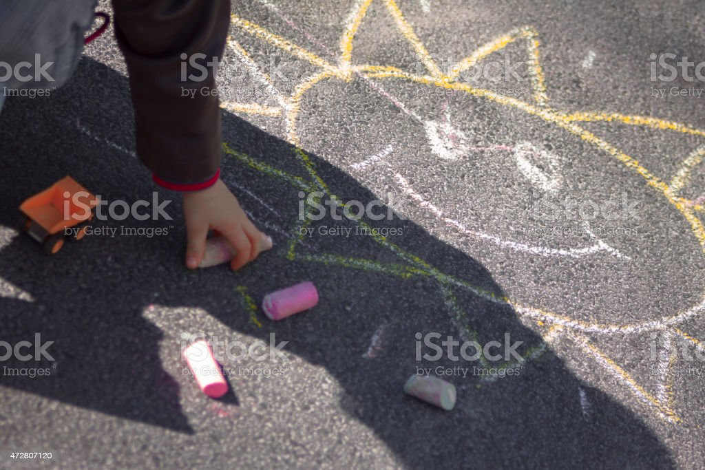 Child playing with sidewalk chalk and sunshine smiley stock photo
