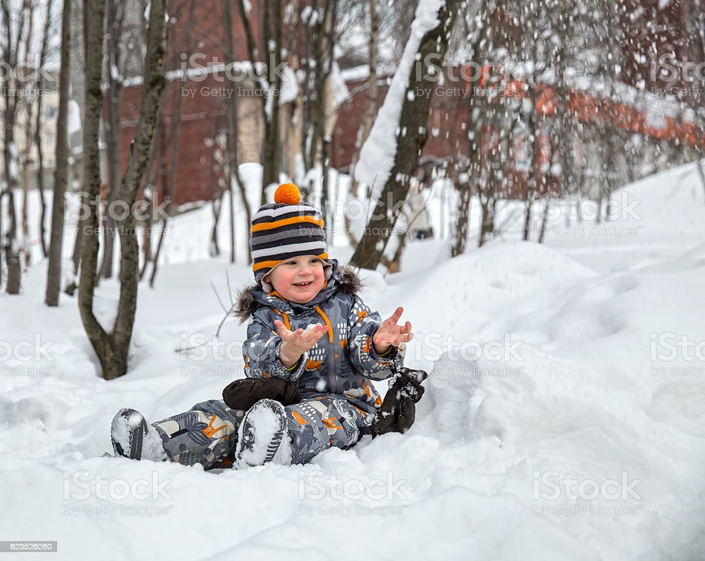 Child playing with snow in winter stock photo