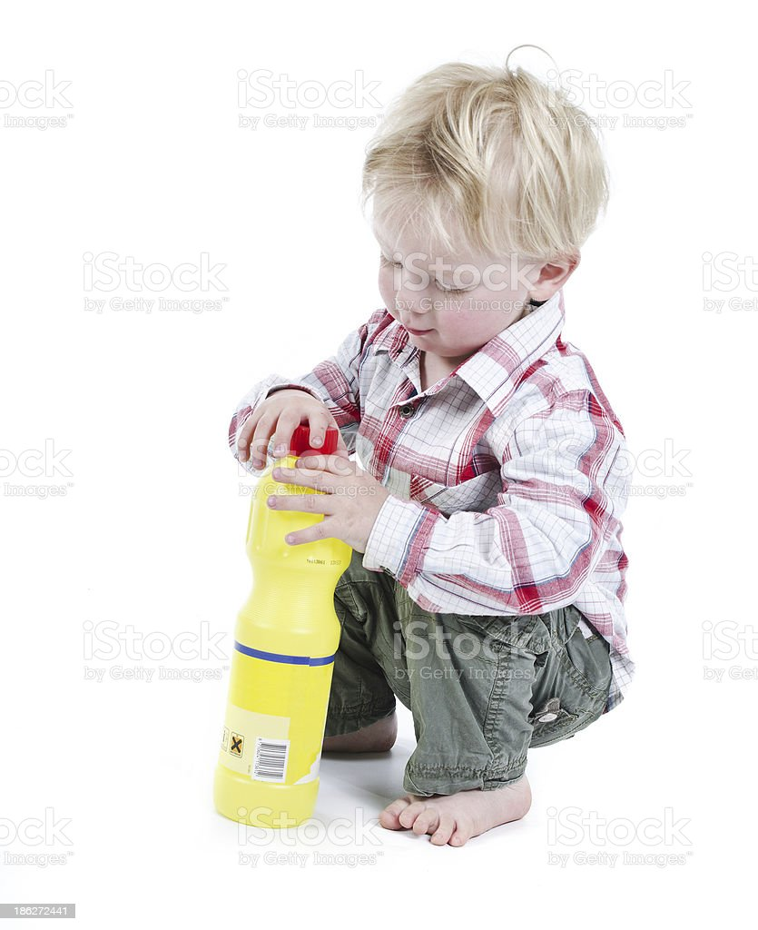 Child playing with toxic cleaners stock photo
