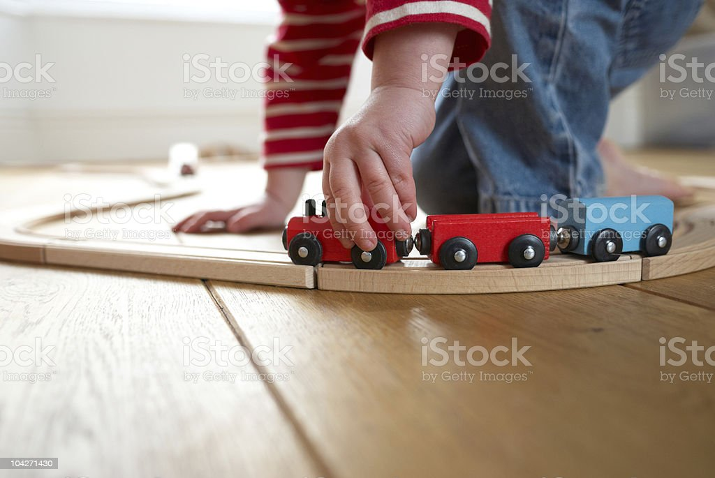Child playing with toy wooden train stock photo