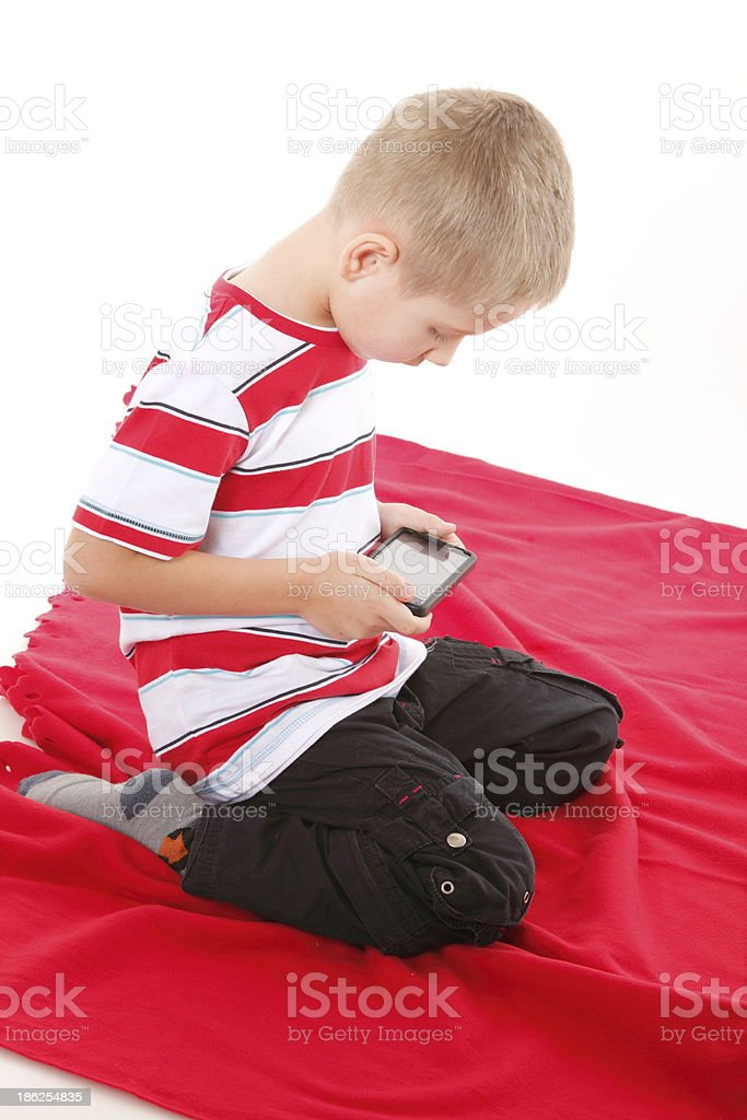 Child plays games on the mobile phone royalty-free stock photo