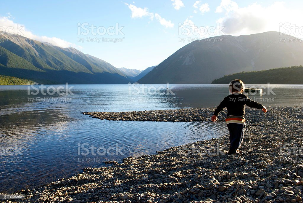 Child plays in Lake at Sunset stock photo