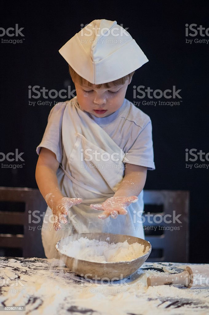 child plays with the flour stock photo