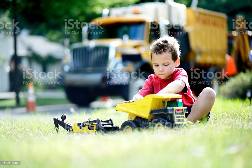 Child plays with toy construction vehicles near the real trucks stock photo