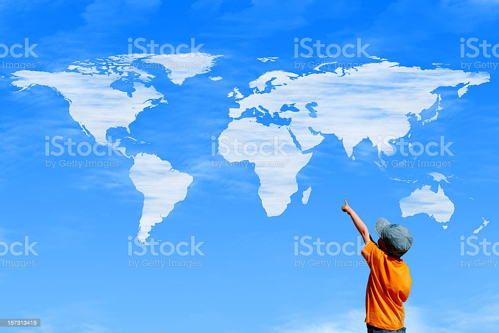 Child pointing at a sky with world map as clouds stock photo