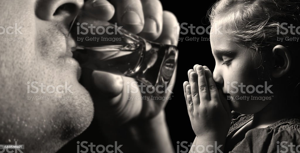 Child prays that father stopped drinking alcohol. stock photo