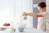 Child preparing cookies in kitchen