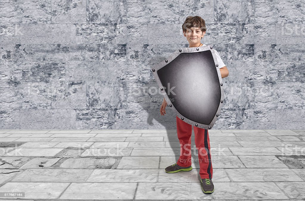 Child protecting himself with a silver shield stock photo