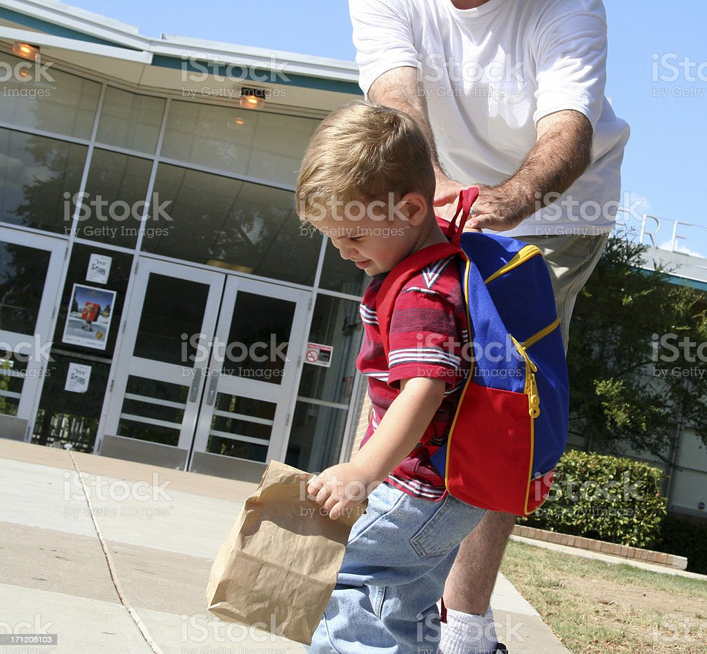 Child pulling away from father at school building royalty-free stock photo